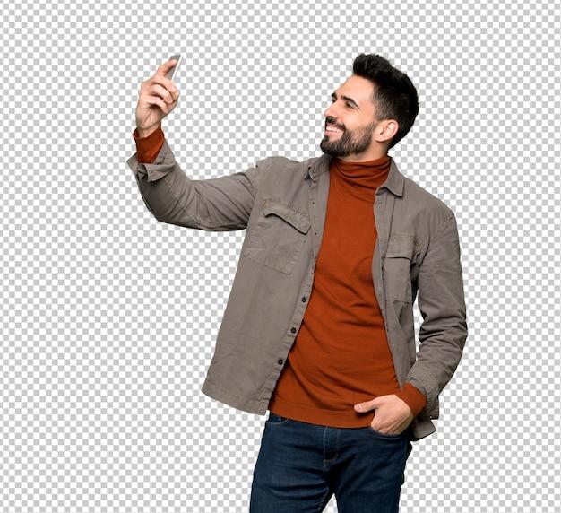 Przystojny mężczyzna z brodą robi selfie
