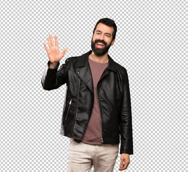 Przystojny mężczyzna z brodą salutuje z ręką z szczęśliwym wyrażeniem