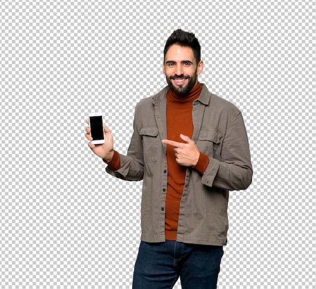 Przystojny mężczyzna z brodą szczęśliwą i wskazującą na telefon komórkowy