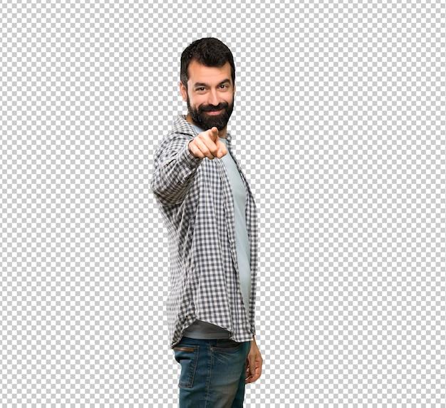 Przystojny mężczyzna z brodą wskazuje palcem na ciebie z pewną miną