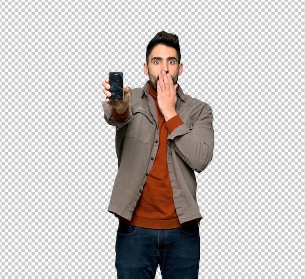 Przystojny mężczyzna z brodą z skołatanym mienia łamającym smartphone