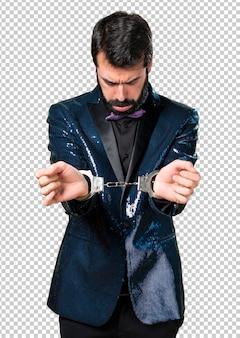Przystojny mężczyzna z cekinową kurtkę z kajdankami