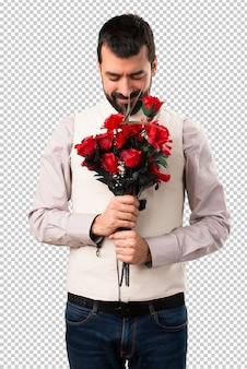 Przystojny mężczyzna z kamizelki mienia kwiatami