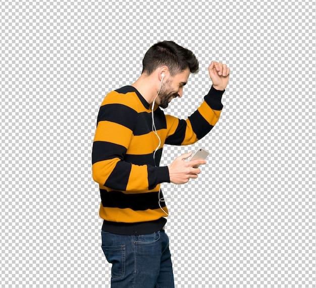 Przystojny mężczyzna z pasiastą pulower słuchającą muzyką z telefonem