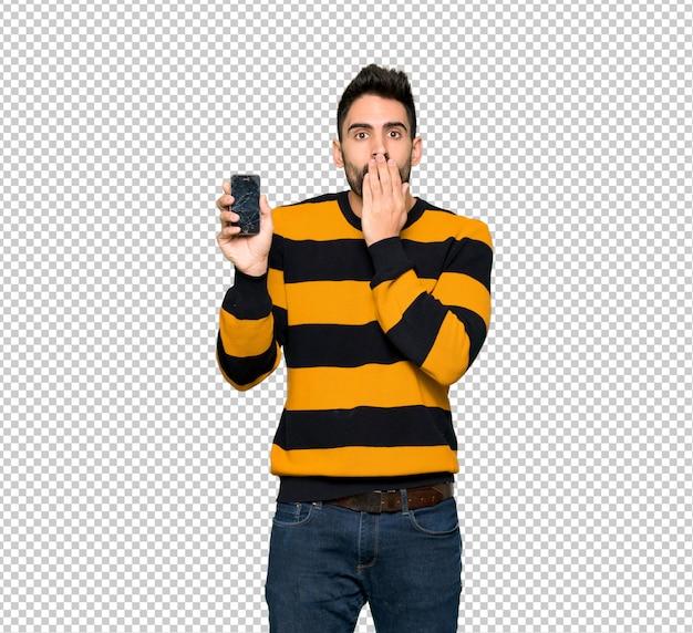 Przystojny mężczyzna z pasiastym pulowerem z niepokojącym mienia łamającym smartphone