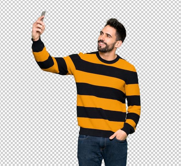 Przystojny mężczyzna z pasiastym swetrem robi selfie