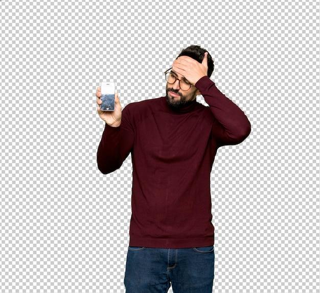 Przystojny mężczyzna z szkłami z skołatanym mienia łamającym smartphone