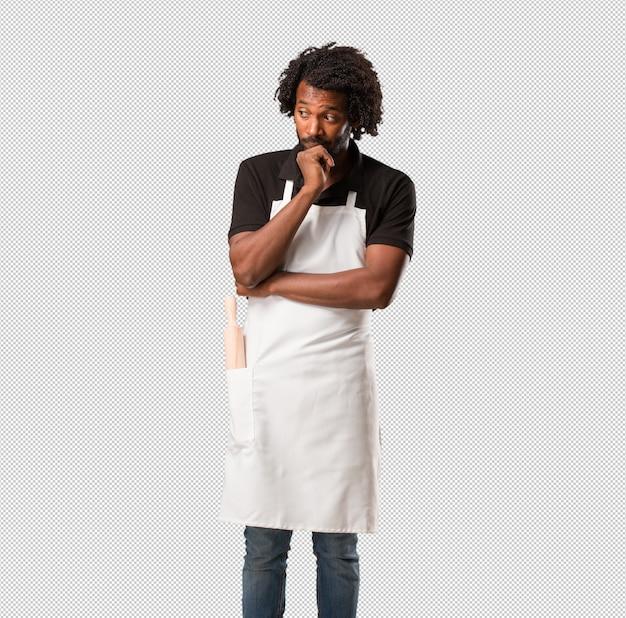 Przystojny piekarz afroamerykanin wątpi i zdezorientowany, myśląc o pomyśle lub martwiąc się o coś