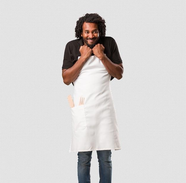 Przystojny piekarz afroamerykański bardzo szczęśliwy i podekscytowany, podnoszący ramiona, świętujący zwycięstwo lub sukces