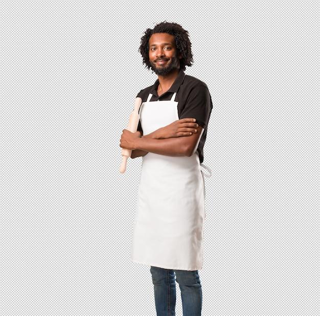 Przystojny piekarz afroamerykański krzyżujący ramiona, uśmiechnięty i szczęśliwy, pewny siebie i przyjazny