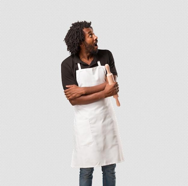 Przystojny piekarz afroamerykański patrząc w górę, myśląc o czymś zabawnym i mając pomysł, wyobraźnię, szczęśliwy i podekscytowany