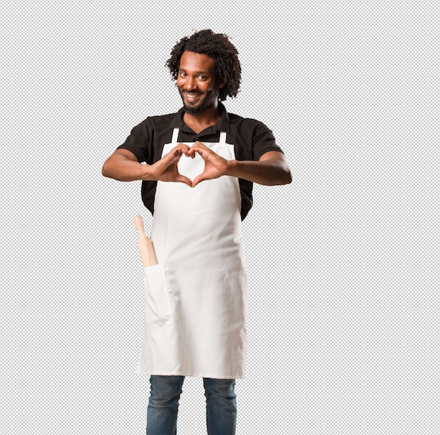 Przystojny piekarz afroamerykański robi serce rękami, wyrażając miłość i przyjaźń, szczęśliwy i uśmiechnięty