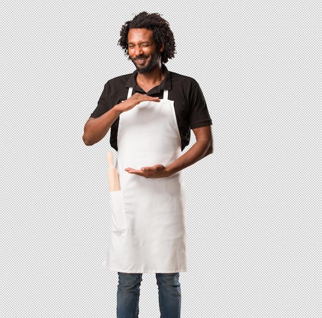 Przystojny piekarz afroamerykański trzymający coś rękami, pokazujący produkt, uśmiechnięty i wesoły, oferujący wyimaginowany przedmiot