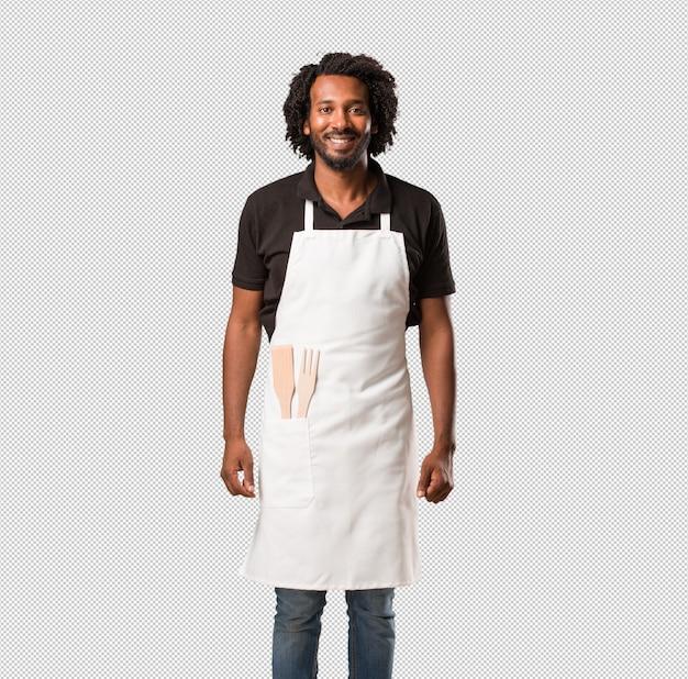 Przystojny piekarz afroamerykański wesoły iz szerokim uśmiechem, pewny siebie, przyjazny i szczery, wyrażający pozytywność i sukces