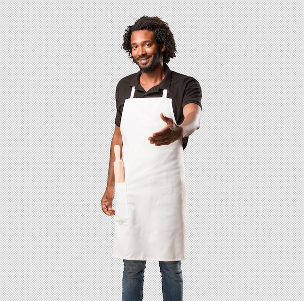 Przystojny piekarz afroamerykański wyciąga rękę, by kogoś przywitać lub gestem pomaga, szczęśliwy i podekscytowany