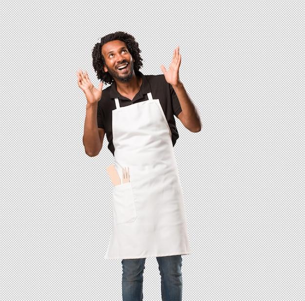 Przystojny piekarz afroamerykański zaskoczony i zszokowany, z szeroko otwartymi oczami, podekscytowany ofertą lub nową pracą, wygrywa koncepcję