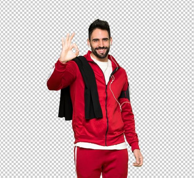 Przystojny sportman pokazuje ok znaka z palcami