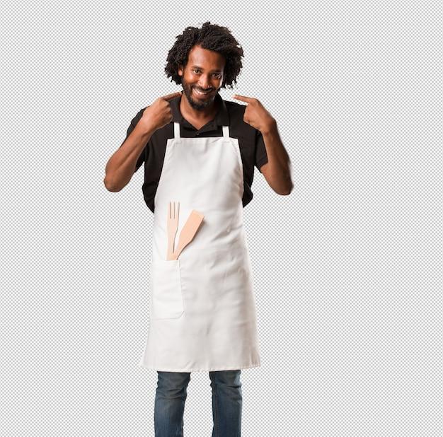 Przystojny uśmiechnięty piekarz afroamerykański, wskazując usta, koncepcja idealnych zębów, białe zęby, jest wesoły i wesoły