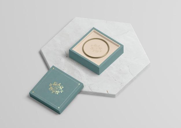 Pudełko na biżuterię ze złotą bransoletką na marmurze