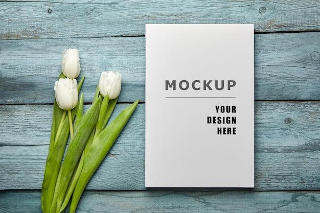 Puste płótno makieta i białe tulipany kwiaty na starej jasnoniebieskiej drewnianej powierzchni leżącej płasko