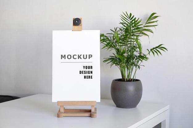 Puste rozciągnięte płótno makieta na drewnianej sztaludze i zielonej rośliny doniczkowej na białym stole