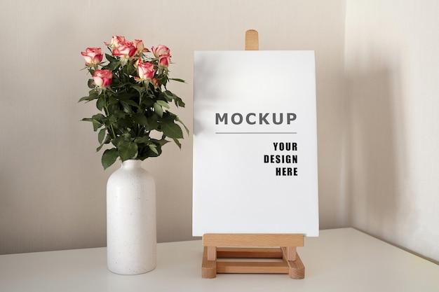 Puste rozciągnięte płótno makieta na drewnianej sztaludze na białym stole z różami w wazonie