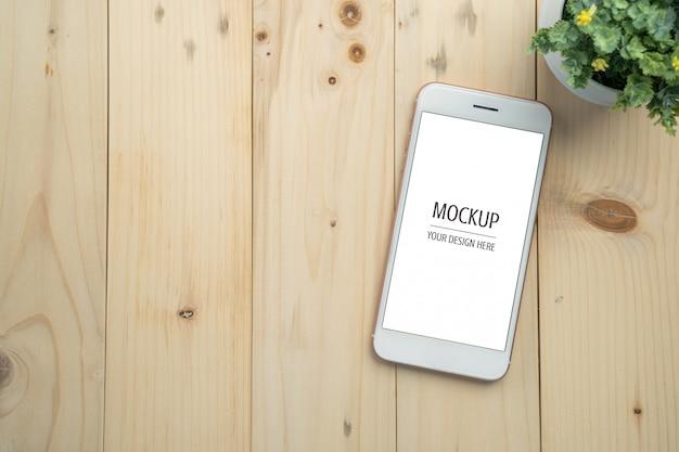 Pusty biały ekran smartphone makieta na stół z drewna
