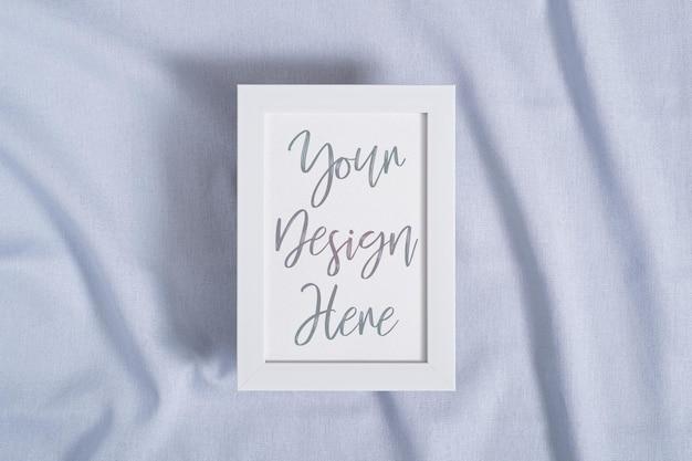 Ramka na zdjęcia z makietą pustej karty papieru na niebieskim, neutralnym kolorze tkaniny