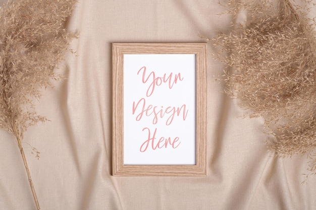 Ramka na zdjęcia z makietą pustej karty papieru w pobliżu suchej trawy pampasów na beżowym neutralnym kolorze tkaniny