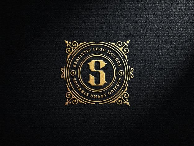Realistyczna luksusowa makieta z wytłoczonym złotym logo na ciemnej ścianie