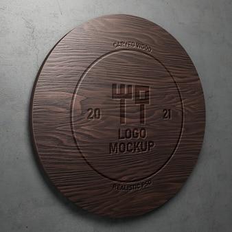 Realistyczna makieta logo z rzeźbionym grawerowanym efektem tekstowym na wypolerowanej, okrągłej perspektywie drewna