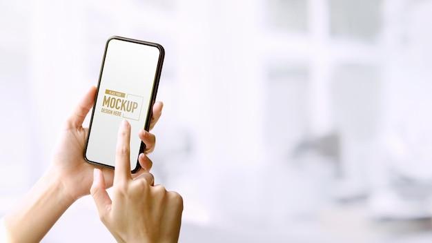 Ręce posiadające i dotykające makiety smartfona