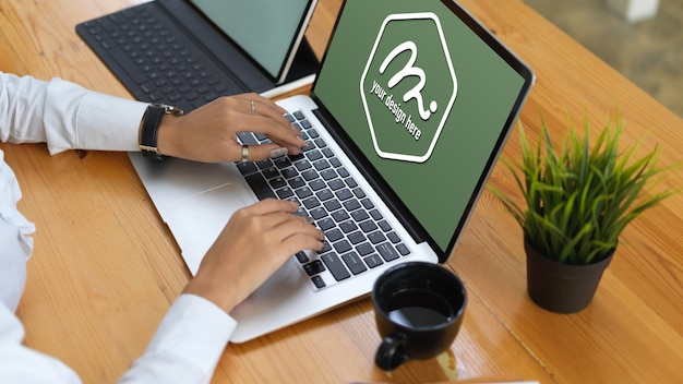 Ręce wpisując na klawiaturze laptopa makiety w pobliżu filiżanki kawy