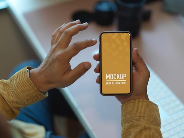 Ręce za pomocą makiety smartfona na stole roboczym