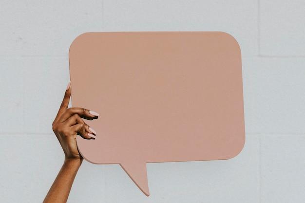 Ręka pokazuje pustą makietę bańki mowy