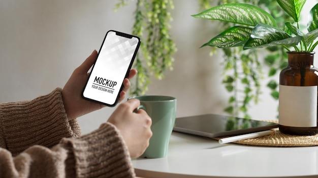 Ręka przy użyciu makiety smartfona na stoliku do kawy