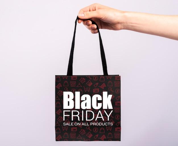 Ręka trzyma czarną małą papierową torbę