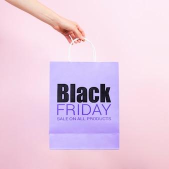 Ręka trzyma czarną piątek papierową torbę
