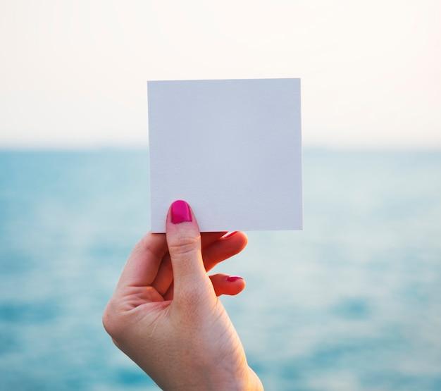 Ręka trzyma dziurkowaty papier rama z oceanu tłem