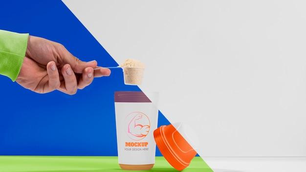 Ręka trzyma łyżkę fitness wypełnione białkiem