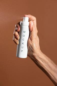 Ręka trzyma makieta białej butelki z aerozolem