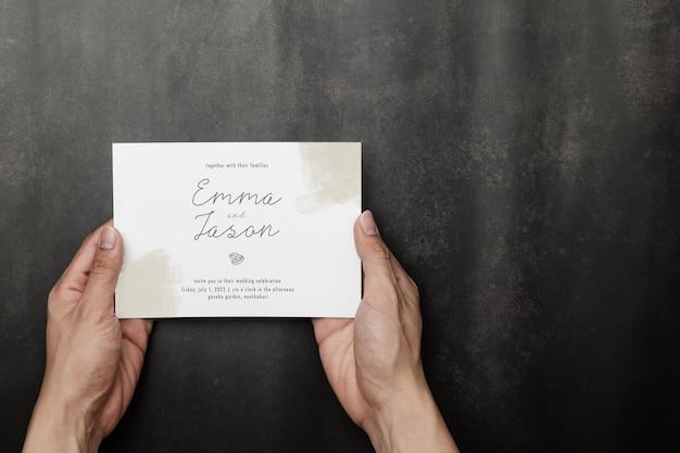 Ręka trzyma makieta karty zaproszenia ślubne, odwiedź szablon karty.