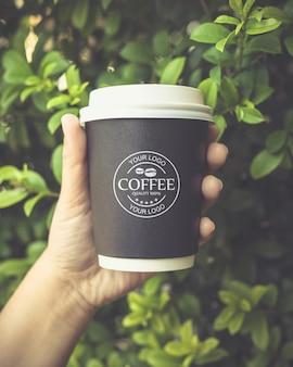 Ręka trzyma makieta papierowy kubek kawy