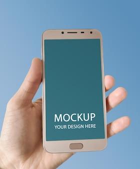 Ręka trzyma makieta smartfona na białym tle