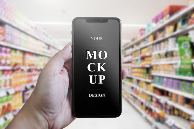 Ręka trzyma mobilną makietę w supermarkecie