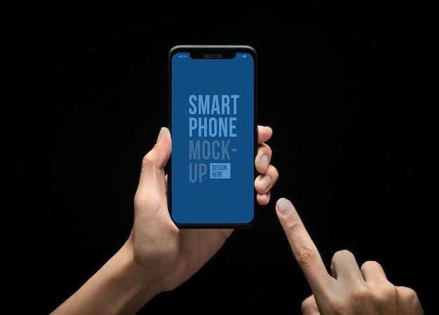 Ręka trzyma nowoczesny smartfon i dotykając ekranu makieta szablon