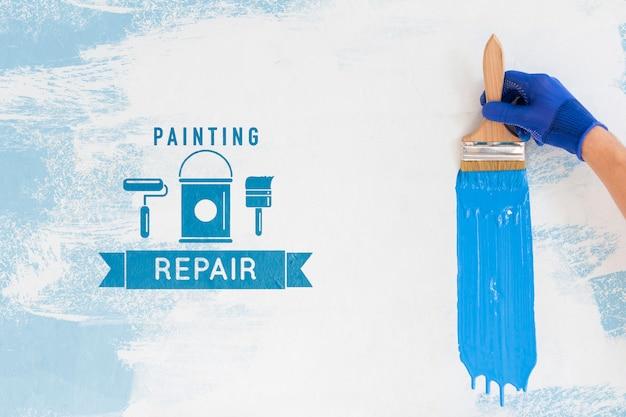 Ręka trzyma pędzel z makiety niebieskiej farby