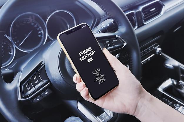 Ręka trzyma smartphone w makieta sceny samochodu