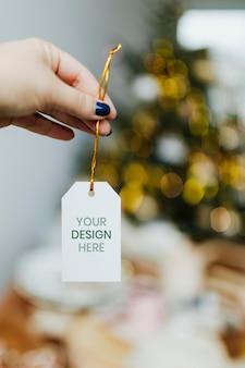 Ręka trzyma szablon tagu świątecznego
