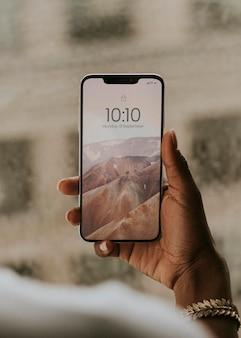 Ręka trzymająca smartfona przy makiecie okna